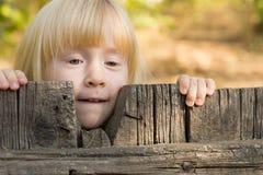 Recht kleines blondes Mädchen, das über einem Zaun blickt Lizenzfreie Stockbilder