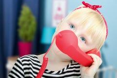 Recht kleines blondes Mädchen mit einem roten Retro- Telefon Stockbild