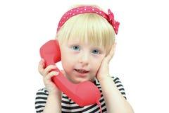 Recht kleines blondes Mädchen mit einem roten Retro- Telefon Lizenzfreie Stockfotos