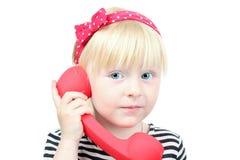 Recht kleines blondes Mädchen mit einem roten Retro- Telefon auf einem weißen BAC Stockbilder