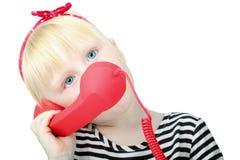 Recht kleines blondes Mädchen mit einem roten Retro- Telefon, lokalisiert auf a Stockbild