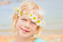 Recht kleines blondes Mädchen mit einer Krone von Gänseblümchen Stockbilder