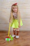 Recht kleines blondes Mädchen, welches das Haus säubert Lizenzfreies Stockfoto