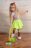 Recht kleines blondes Mädchen, welches das Haus säubert Stockfoto