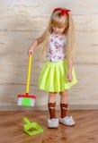 Recht kleines blondes Mädchen, welches das Haus säubert Stockfotografie