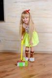 Recht kleines blondes Mädchen, welches das Haus säubert Stockfotos