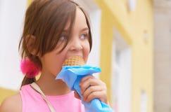Recht kleines Mädchen, das große Eiscreme im glücklichen Lachen des Waffelkegels auf Naturhintergrund leckend isst stockfotos