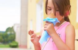 Recht kleines Mädchen, das große Eiscreme im glücklichen Lachen des Waffelkegels auf Naturhintergrund leckend isst stockfotografie