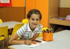 Recht kleines Mädchen beim Zeichnen mit den Bleistiftfarben am scho Lizenzfreies Stockbild
