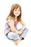 Recht kleines Mädchen, das auf dem Fußboden in den Jeans sitzt Stockbilder