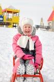 Recht kleines Mädchen, das auf einem Schlitten im Schnee spielt Lizenzfreies Stockbild