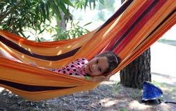 Recht kleines Mädchen, das in der Hängematte im Erholungsort stillsteht Lizenzfreies Stockfoto