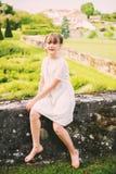 Recht kleines Mädchen, das in einem schönen Garten spielt Lizenzfreie Stockfotos