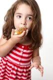 Recht kleines Mädchen, das einen Krapfen isst Stockfotografie