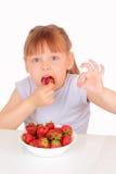 Recht kleines Mädchen, das Erdbeeren isst stockfotografie