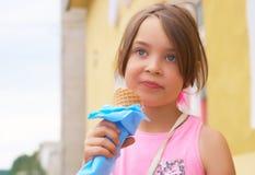 Recht kleines Mädchen, das große Eiscreme im glücklichen Lachen des Waffelkegels auf Naturhintergrund leckend isst lizenzfreie stockfotos