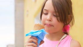 Recht kleines Mädchen, das große Eiscreme im glücklichen Lachen des Waffelkegels auf Naturhintergrund leckend isst lizenzfreies stockfoto