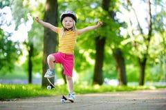 Recht kleines Mädchen, das lernt, draußen Skateboard zu fahren Lizenzfreies Stockfoto