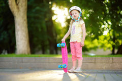 Recht kleines Mädchen, das lernt, am schönen Sommertag in einem Park Skateboard zu fahren Kind, das Fahrt draußen Skateboard fahr Stockbild