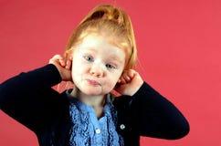 Recht kleines Mädchen, das lustiges Gesicht bildet Lizenzfreie Stockfotografie