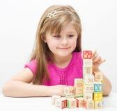 Recht kleines Mädchen, das mit hölzernen Würfeln mit Buchstaben und Zahlen spielt Stockfotografie