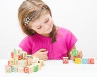 Recht kleines Mädchen, das mit hölzernen Würfeln mit Buchstaben und Zahlen spielt Lizenzfreies Stockbild