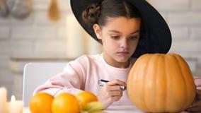 Recht kleines Mädchen, das Steckfassungskürbis macht und für Halloween-Vorabendpartei sich vorbereitet stockbilder