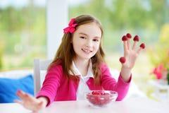 Recht kleines Mädchen, das zu Hause Himbeeren isst Nettes Kind, das ihre gesunden frischen Früchte und Beeren genießt Lizenzfreie Stockfotografie