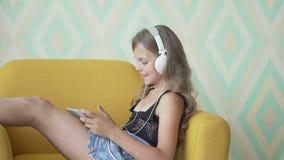 Recht kleines Mädchen in den Kopfhörern hört Musik unter Verwendung einer Tablette, beim auf Sofa zu Hause sitzen stock footage