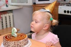 Recht kleines Mädchen in der Geburtstagschutzkappe und -kuchen. Lizenzfreies Stockfoto