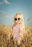 Recht kleines Mädchen in der modischen gelben Sonnenbrille Stockfotos
