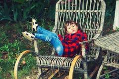 Recht kleines Mädchen in einem Stuhl im Garten stockfotos