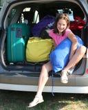 Recht kleines Mädchen füllt die Koffer auf dem Auto Stockfoto