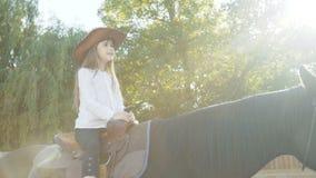 Recht kleines Mädchen im Hut, der eine schwarze Stute auf die Arena reitet 4K stock video