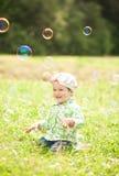 Recht kleines Mädchen ist, spielend lachend und mit Seifenblasen Lizenzfreies Stockbild