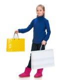 Recht kleines Mädchen mit Einkaufstaschen Stockfoto
