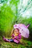 Recht kleines Mädchen mit Regenschirm im Park Stockfoto