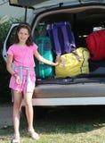 Recht kleines Mädchen mit rosa Kleid lädt Koffer auf dem Auto Stockfotografie