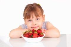 Recht kleines Mädchen und Platte mit Erdbeeren stockfotos