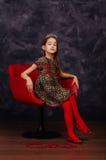 Recht kleines Mädchen, welches das schöne Kleid sitzt im roten Lehnsessel trägt Sie trägt rote Maskeradekarnevalsmaske Schönes Ta Lizenzfreie Stockfotografie