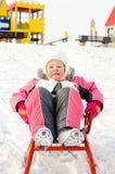 Recht kleines Mädchen, das auf einem Schlitten im Schnee spielt Lizenzfreies Stockfoto