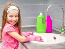 Kleines Mädchen, das die Teller wäscht Stockbilder