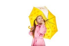 Recht kleines Mädchen mit gelbem Regenschirm auf Weiß Stockfotos