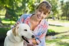 Recht lächelnde blonde Aufstellung mit ihrem Labrador im Park Lizenzfreies Stockfoto