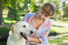 Recht lächelnde blonde Aufstellung mit ihrem Labrador im Park Lizenzfreie Stockbilder