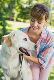 Recht lächelnde blonde Aufstellung mit ihrem Labrador im Park Stockfoto