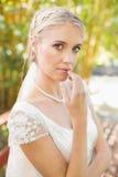 Recht lächelnde blonde Braut, die auf einer Brücke betrachtet Kamera steht Stockfotografie