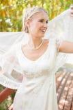 Recht lächelnde blonde Braut, die heraus ihren Schleier hält Stockfotos