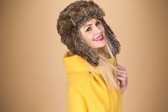Recht lächelnde blonde Frau in einem Winterhut Stockbild