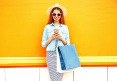 recht lächelnde junge Frau benutzt den Smartphone in der Stadt Stockbild